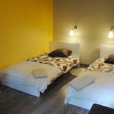 La chambre jaune à l'étage avec deux lits simples